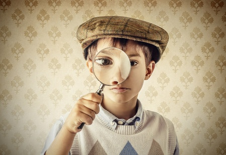 This is photo of a young boy wearing a Sherlock Holmes style hat. He is holding a magnifying glass to his eye, as though he is looking for clues.
