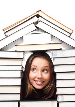 This is a photo of a house made out of books. There is a roof and walls. The center is open. A young woman smiling face is in the middle of the structure.
