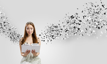 This is a photo of a young woman reading a book. She appears to be in deep concentration. Letters are pouring out of the books and surrounding her.